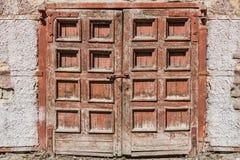 En gammal retro sjaskig trämålad brun dubbel dörr med ett lås och ett fragment av en gammal packad vägg med kala tegelstenar arkivfoto
