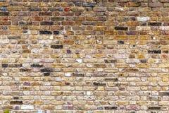 En gammal, riden ut brun tegelstenvägg arkivfoton