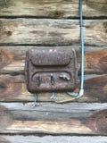 En gammal rost-täckt elektrisk klaff på väggen av ett träskjul Elektriskt ledningsnät och plast- strömbrytare är synliga royaltyfria foton