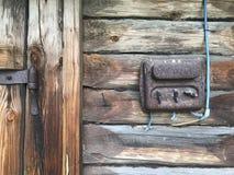 En gammal rost-täckt elektrisk klaff på väggen av ett träskjul Elektriskt ledningsnät och plast- strömbrytare är synliga arkivbilder