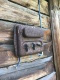 En gammal rost-täckt elektrisk klaff på väggen av ett träskjul Elektriskt ledningsnät och plast- strömbrytare är synliga royaltyfri foto