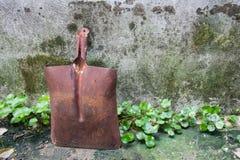 En gammal rostig skyffel bredvid betongväggarna Arkivfoto