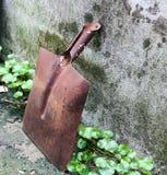 En gammal rostig skyffel bredvid betongväggarna Arkivfoton
