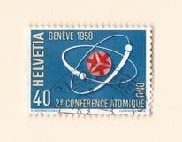 En gammal schweizisk portostämpel som firar minnet av atom- konferensen den 1958 i geneva Fotografering för Bildbyråer