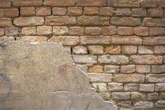 En gammal skadad röd grå tegelstenvägg med bevarat murbrukområde Textur för grov yttersida royaltyfri foto