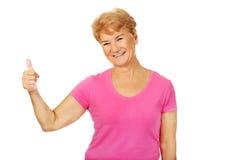 En gammal smiligkvinna med tummen upp Fotografering för Bildbyråer