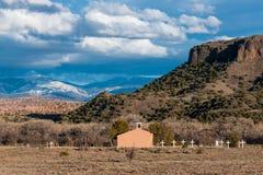 En gammal spansk beskickningstilkyrka med en rad av vita kors i ett sydvästligt landskap av mesas, badlands och berg royaltyfria bilder