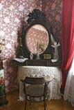 En gammal spegel i en ram på en tabell som täckas med en stucken bordduk arkivfoto