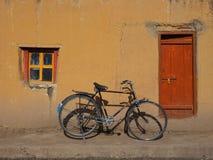 En gammal svart tappningcykel med stora hjul står nära den gula väggen mellan fönstret med en träram och en träbro Arkivfoto