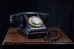 En gammal svart telefon Närbild På en gammal trätabell arkivfoton