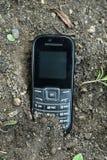 En gammal telefon som begravas i jordningen royaltyfri foto