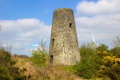 En gammal väderkvarnstubbe i en 19th århundradeledning bryter med moderna vanes för vindturbinen i bakgrunden i nordliga Conlig - Royaltyfri Foto