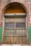 En gammal välvd dörr på en tegelstenbyggnad arkivfoto
