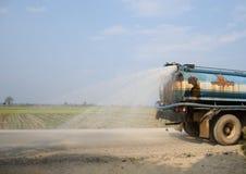 En gammal vattenlastbil som besprutar vatten på den förstörda lantliga vägen Arkivbild