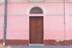 En gammal wood dörr på den rosa väggen Arkivfoto