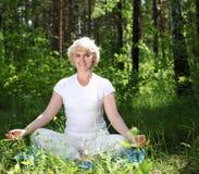 En gammalare kvinna övar yoga Fotografering för Bildbyråer