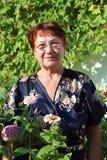 En gammalare kvinna i trädgården royaltyfri bild