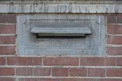 En gammalmodig antik brevlåda (eller brevlåda, postbox, brevlåda) placeras i en vägg för röd tegelsten Royaltyfri Foto