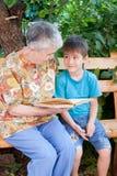 En gammelmormor läser en bok till barnbarnsbarnet Royaltyfri Bild
