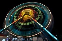 En ganska ritt sköt med en lång exponering på natten - pariserhjul i aftonen som skapar ljusa strimmor Arkivfoto