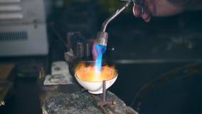 En gasbrännare riktas in i en mycket liten smyckenplatta JuvelerareWorking smycken