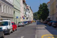 En gata i Graz Österrike med träd som så är högväxta som byggnaderna Royaltyfri Fotografi