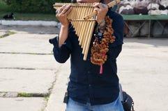 En gataaktör från Peru som utför latin - amerikansk musik på traditionella instrument på gatan arkivfoto