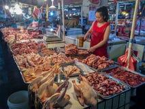 En gataköttförsäljare arbetar i en lokal marknad i Kina Royaltyfri Bild