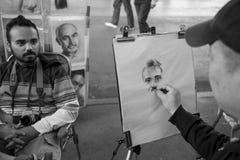 En gatakonstnär drar en karikatyr Arkivfoton