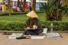 En gatakonstnär som drar bulidings arkivfoton
