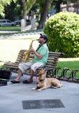 En gatamusiker som spelar saxofonen i parkera En busker med hans gulliga hund royaltyfri foto