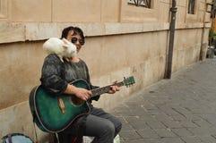 En gatamusiker spelar gitarren och rymmer en vit kanin på hans skuldra för underhållningen av turister i mitten arkivfoto