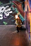 En gatamusiker spelar en tuba med brand i stadmarknaden framme av en vägg med grafitti byggnadskungarikelondon gammalt torn eniga royaltyfri foto