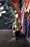 En gatamusiker spelar en tuba med brand i stadmarknaden framme av en vägg med grafitti byggnadskungarikelondon gammalt torn eniga royaltyfri fotografi