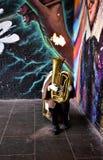 En gatamusiker spelar en tuba med brand i stadmarknaden framme av en vägg med grafitti byggnadskungarikelondon gammalt torn eniga fotografering för bildbyråer