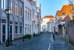 En gatasikt med pittoreska historiska hus, gamla lyktor och två att närma sig cykla damer på det annat slutet av gatan royaltyfri bild