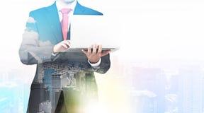 En genomskinlig kontur av en man i den formella dräkten som söker efter några data i bärbara datorn Arkivbilder