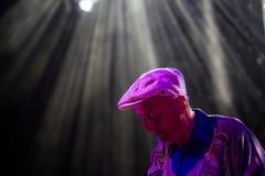 En gentleman som sjunger med en mikrofon i en strålkastare Royaltyfri Bild