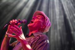 En gentleman som sjunger med en mikrofon i en strålkastare Royaltyfria Foton