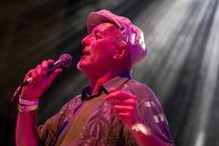 En gentleman som sjunger med en mikrofon i en strålkastare Arkivbild