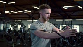 En gimnasio el hombre fuerte tira del brazo de la máquina del entrenamiento en una dirección metrajes