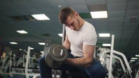 En gimnasio el hombre sienta y levanta una pesa de gimnasia con una mano El culturista joven realiza ejercicios en bíceps con la  metrajes