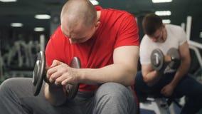 En gimnasio el hombre sienta y levanta una pesa de gimnasia con una mano El culturista joven realiza ejercicios en b?ceps con la  almacen de metraje de vídeo