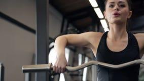 En gimnasio la mujer hermosa aumenta la barra con un cuello curvado almacen de video