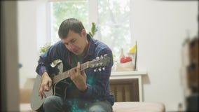 En gitaarspeler die spelen zingen mens die akoestische gitaar langzame geanimeerde video spelen in de ruimte zit levensstijl op stock video