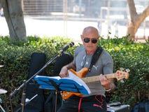 En gitarrist från en grupp av gatamusiker spelar musik för förbipasserande i Tel Aviv, Israel arkivfoto