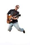 En gitarrist hoppar med hans gitarr arkivbilder