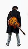 En gitarrist med hans gitarr i baksidan arkivfoto