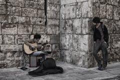 En gitarrist spelar i gatan, medan folket lyssnar arkivfoto