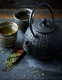 En gjutjärntekruka och ett grönt te i keramiska koppar Arkivbilder